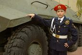 stock photo of army cadets  - Young cadet standing near an armored troop carrier - JPG
