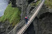 image of irish moss  - man crossing a rope bridge in Ireland - JPG