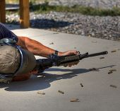 stock photo of ar-15  - Competitive shooter on the ground on his right side with brass bouncing away - JPG