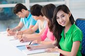 stock photo of adolescent  - Row of students sitting in classroom and writing - JPG