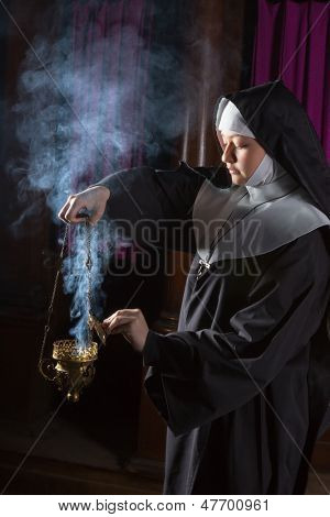 Young nun preparing an incense burner for mass