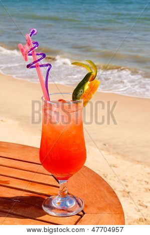 Tequila Sunrise cocktail on the wooden table with crushed ice