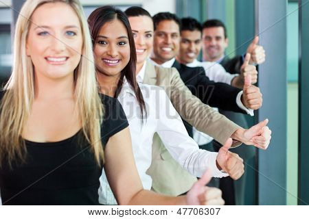 row of smiling business team giving thumbs up