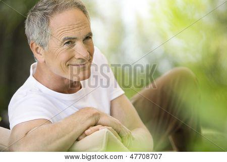 Glücklicher mittleren Alter Mann liegend auf Liegestuhl im Garten