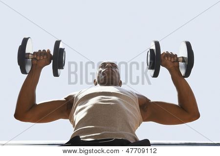 Low angle view of muscular man lifting dumbbells against sky