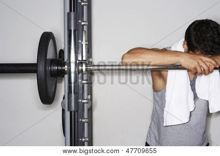 Tired young man resting on barbell after workout at gym
