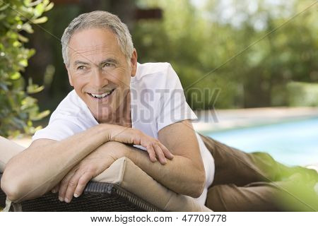 Cheerful middle aged man reclining on deck chair in garden