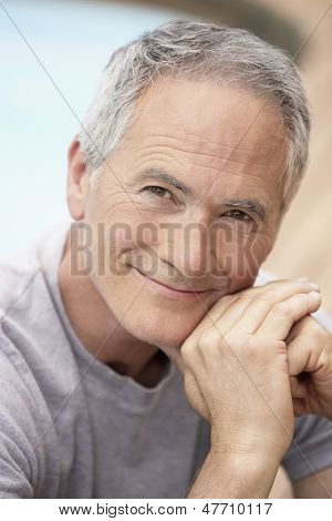 Closeup portrait of middle aged man relaxing by pool
