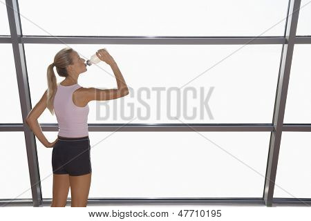 Rear view of fit young woman in sportswear drinking water by window in gym