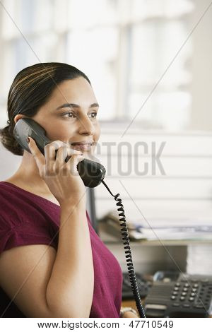Portrait of young Asian businesswoman using landline phone at desk