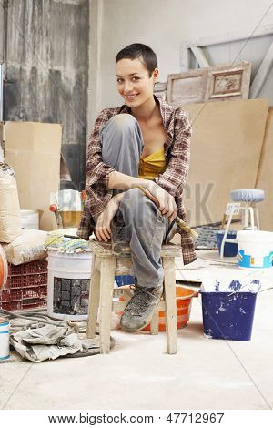 Portrait of young female painter sitting on stool in work site