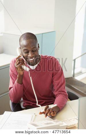 Smiling African American businessman using landline at desk