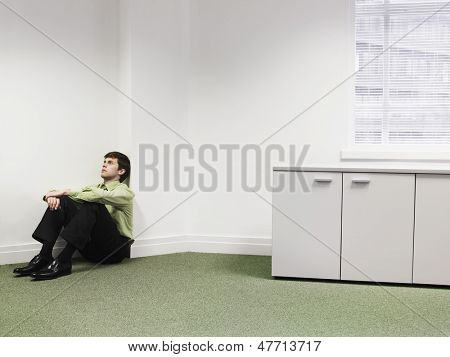 Upset young businessman sitting on floor in the corner at office