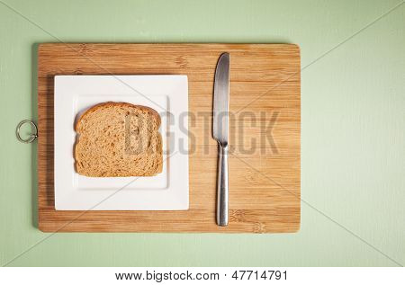 Sliced Brown Bread On Square White Plate With Knife