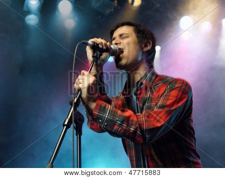 Low angle view of a young man singing into microphone on stage