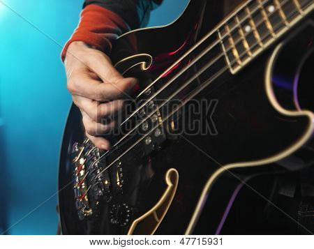 Closeup of a hand playing the bass guitar