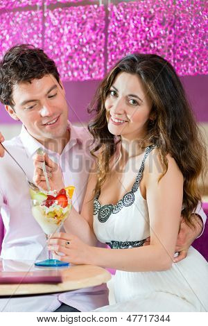 Young Couple in a Cafe or Ice cream parlor, eating an ice cream sundae together