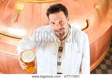 Man in Lab coat, a Brewer, with beer stein in brewery
