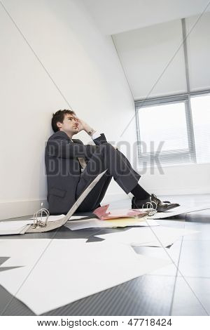 Stressed businessman sitting on floor by scattered files in empty office