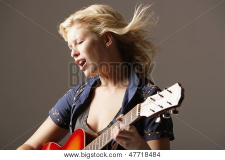 Woman playing guitar and singing with windblown hair