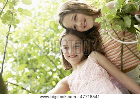 Low angle view of two girls smiling in the backyard