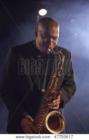 Jazz musician playing saxophone on smokey stage