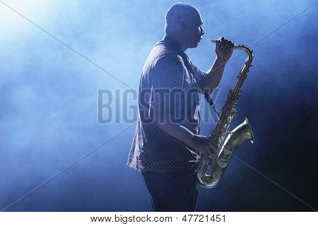 Side view of an African American man playing saxophone against smoky background
