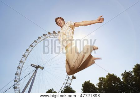 Low angle view of a young man jumping in front of London Eye in park