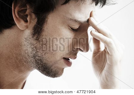 Side view of young man with headache touching forehead on white background