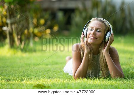 Happiness girl with headphones enjoying music and nature at sunny day
