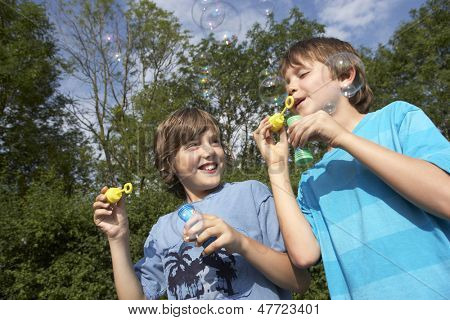 Low angle view of two young boys blowing soap bubbles in park