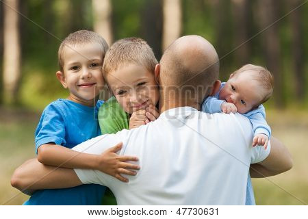 Family happiness - loving father bonding or holding little smiling sons and newborn baby