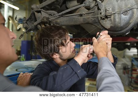 Mechanics teacher with student in car repairshop