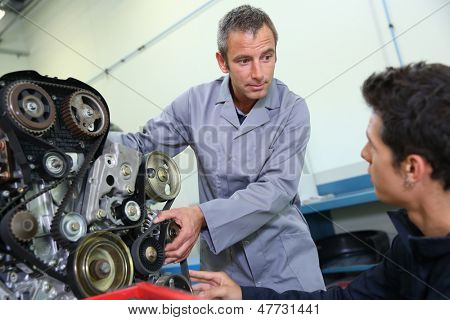 Professional trainer teaching student how to fix car engine