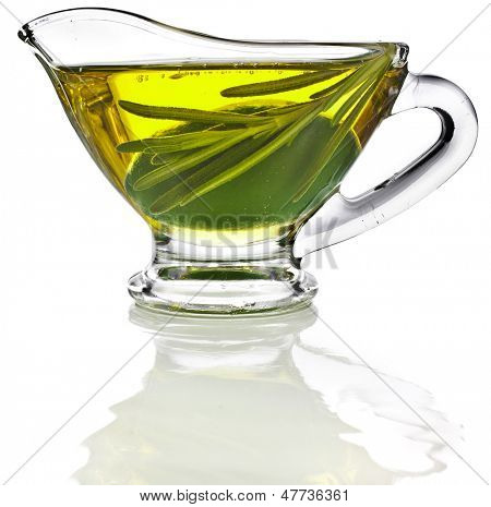 Olive oil sauce with rosemary herbs in the  in gravy boat  isolated on white background
