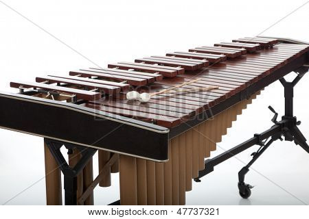 A wooden marimba and mallets on a white background