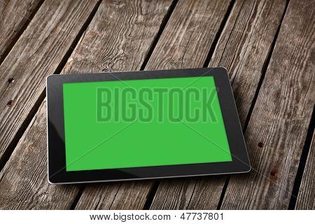 Digital tablet computer with isolated screen on old wooden desk.