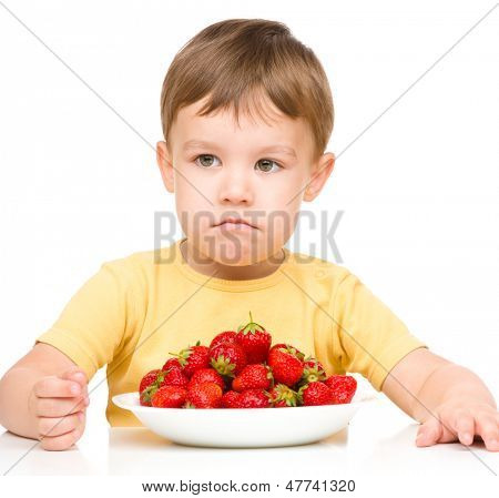 Little boy refuses to eat strawberries, isolated over white