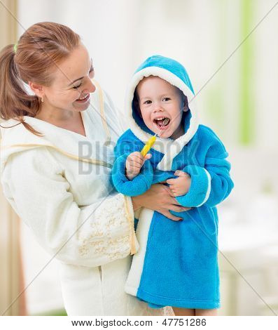 mother and child brushing teeth together in bathroom. Dental hygiene.