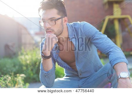 casual young man outdoor standing with his hand on his chin and pensively looking away from the camera