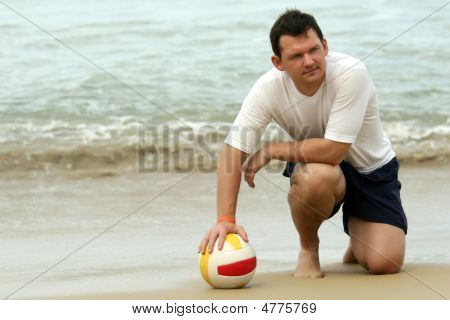 Man With Volleyball On The Beach