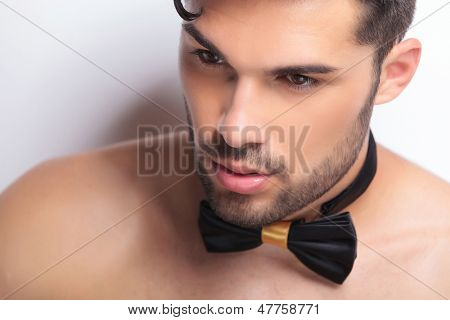 closeup of a young topless man with a bowtie looking away from the camera. on gray background