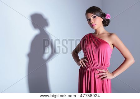 young beauty woman with hands on hips is looking at the camera. on a light gray background with shadow