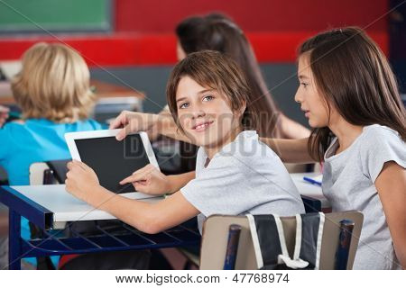 Side view portrait of little boy with girl using digital tablet at desk in classroom