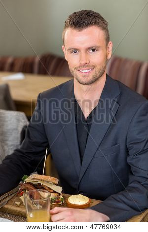 Portrait of young businessman with sandwich and juice in coffeeshop