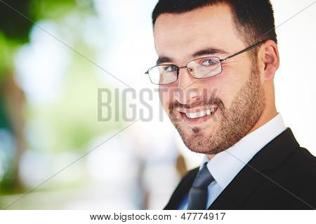 Close-up portrait of a successful business guy smiling ambitiously
