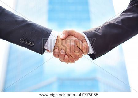 Close-up of business partners shaking hands to do business together