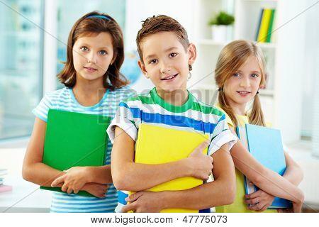 Portrait of three adorable kids holding textbooks
