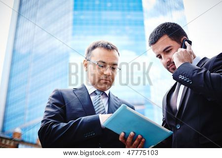 White-collar workers being busy with the project and consulting via mobile