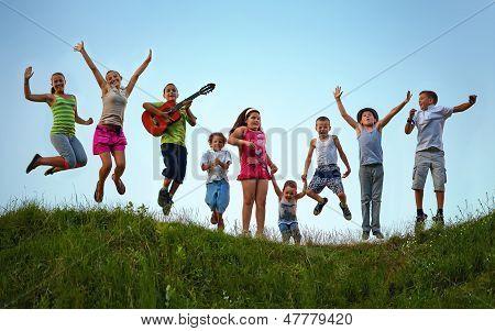 Happy Kids saltando en el campo de verano